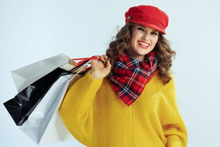 Portrait of smiling modern female with long brunette hair in sweater, scarf and red hat with shopping bags on winter light blue background.