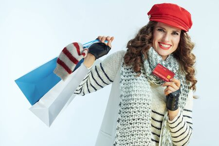 Portrait of smiling trendy woman with long brunette hair in sweater, scarf and red hat with shopping bags with sweaters showing credit card on winter light blue background. Banque d'images