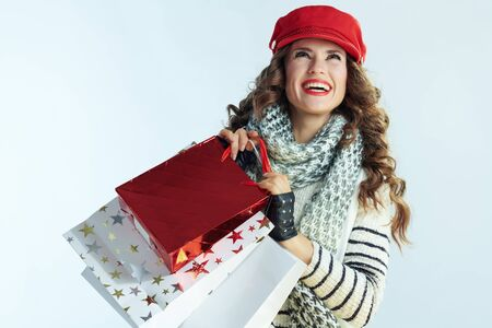 smiling stylish woman with long brunette hair in sweater, scarf and red hat with shopping bags looking up isolated on winter light blue background.