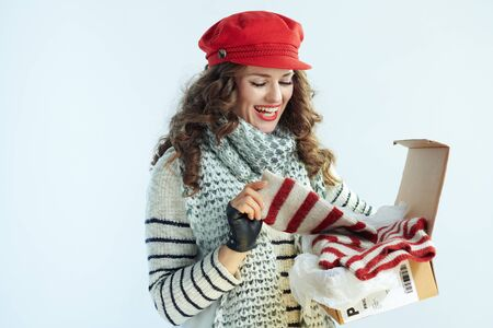 smiling elegant middle age woman with long brunette hair in sweater, scarf and red hat holding opened parcel and checking delivered sweater on winter light blue background.