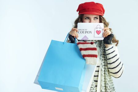 trendy female with long brunette hair in sweater, scarf and red hat with shopping bags with sweaters showing discount coupon isolated on winter light blue background.