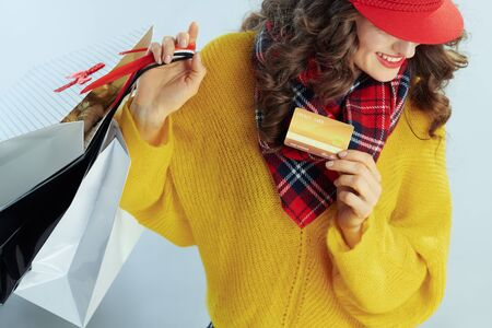 happy trendy 40 years old woman with long brunette hair in sweater, scarf and red hat with shopping bags showing golden credit card against winter light blue background.