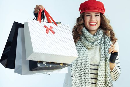 Portrait of smiling modern woman with long brunette hair in sweater, scarf and red hat showing shopping bags against winter light blue background.