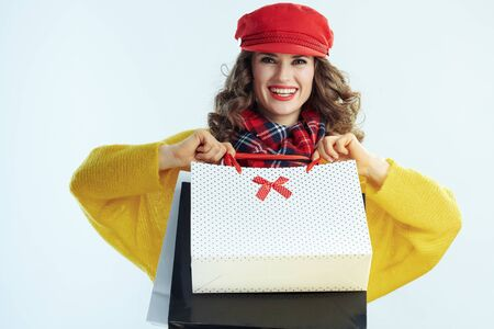 happy elegant 40 years old woman with long brunette hair in sweater, scarf and red hat showing shopping bags isolated on winter light blue background.
