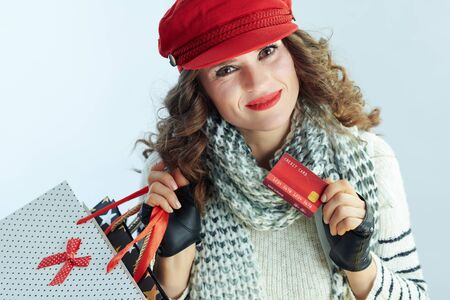 Portrait of smiling trendy female with long brunette hair in sweater, scarf and red hat with shopping bags and credit card isolated on winter light blue background.