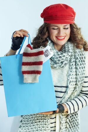 smiling modern female with long brunette hair in sweater, scarf and red hat showing blue shopping bag with purchased sweater against winter light blue background.