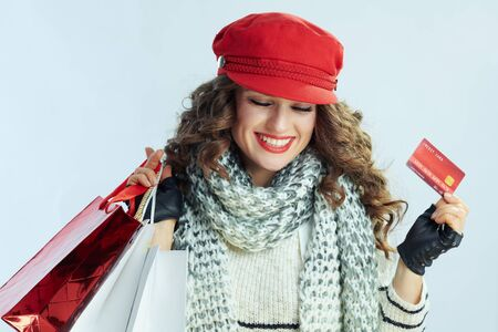 smiling modern middle age woman with long brunette hair in sweater, scarf and red hat with shopping bags and credit card on winter light blue background.