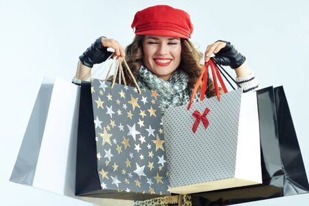 happy young woman with long brunette hair in sweater, scarf and red hat showing shopping bags on winter light blue background.