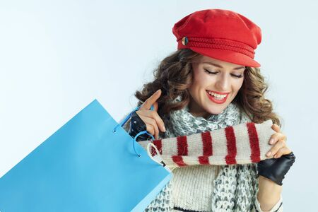 happy trendy woman with long brunette hair in sweater, scarf and red hat with blue shopping bag checking purchases on winter light blue background.