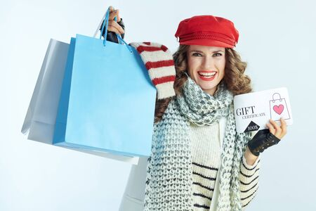 smiling young female with long brunette hair in sweater, scarf and red hat showing shopping bags with sweaters and discount coupon against winter light blue background.