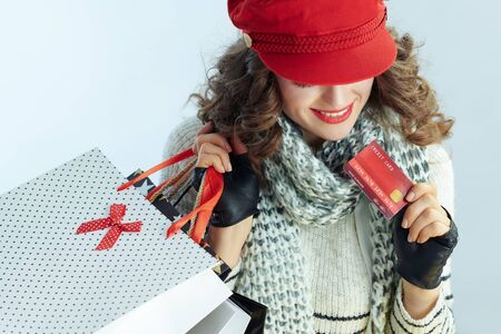 young woman with long brunette hair in sweater, scarf and red hat with shopping bags and credit card on winter light blue background.