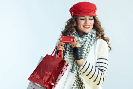 smiling trendy woman with long brunette hair in sweater, scarf and red hat with shopping bags and credit card on winter light blue background.