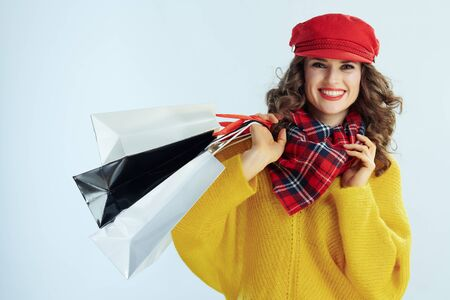 Portrait of happy stylish woman with long brunette hair in sweater, scarf and red hat with shopping bags on winter light blue background. Stock Photo