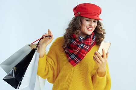 smiling trendy middle age woman with long brunette hair in sweater, scarf and red hat with shopping bags writing sms isolated on winter light blue background.