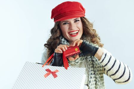 Portrait of happy young 40 years old woman with long brunette hair in sweater, scarf and red hat with shopping bags showing credit card in heart shaped hands isolated on winter light blue background.