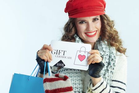Portrait of happy elegant woman with long brunette hair in sweater, scarf and red hat with shopping bags with sweaters showing discount coupon isolated on winter light blue background.