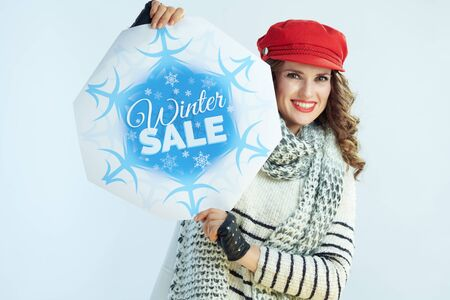 Portrait of smiling trendy woman with long brunette hair in sweater, scarf and red hat showing winter sale banner on winter light blue background.