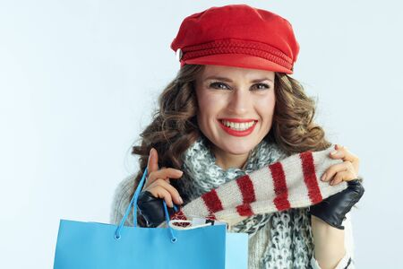 Portrait of happy elegant 40 years old woman with long brunette hair in sweater, scarf and red hat with blue shopping bag showing purchases against winter light blue background.