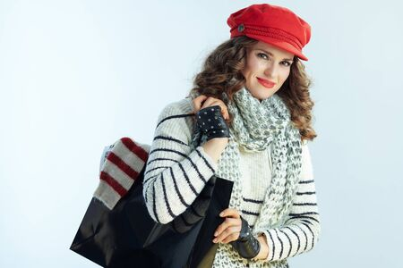 Portrait of stylish female with long brunette hair in sweater, scarf and red hat with black shopping bag with purchased sweater against winter light blue background.