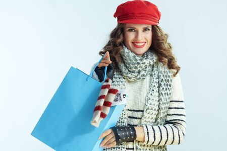 Portrait of smiling elegant middle age woman with long brunette hair in sweater, scarf and red hat with blue shopping bag with purchased sweater isolated on winter light blue background. Stockfoto