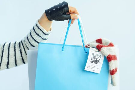 Closeup on young 40 years old woman with long brunette hair in sweater, scarf and red hat with shopping bags with bought sweaters against winter light blue background.