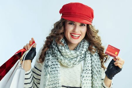 Portrait of happy modern woman with long brunette hair in sweater, scarf and red hat with shopping bags showing credit card against winter light blue background.