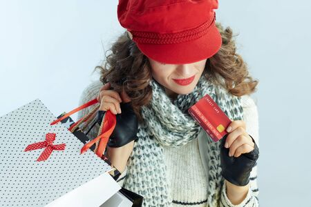 young female with long brunette hair in sweater, scarf and red hat with shopping bags and credit card on winter light blue background.