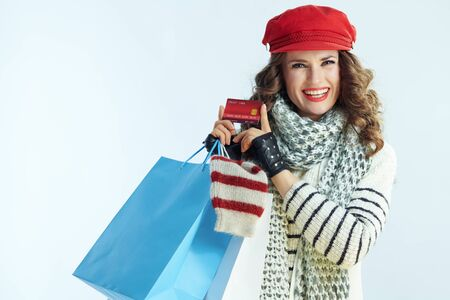 Portrait of happy trendy 40 years old woman with long brunette hair in sweater, scarf and red hat with shopping bags with sweaters showing credit card on winter light blue background.