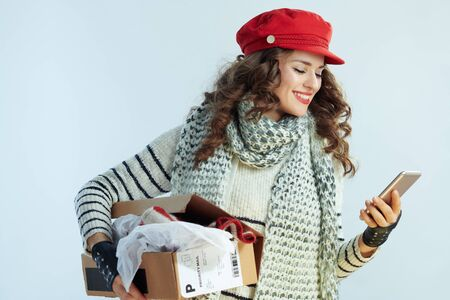 smiling trendy female with long brunette hair in sweater, scarf and red hat holding opened parcel and using smartphone app isolated on winter light blue background.