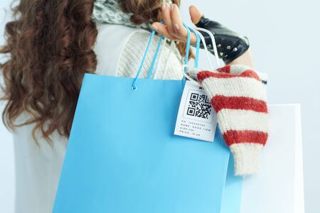 Closeup on young woman with long brunette hair in sweater, scarf and red hat with shopping bags with purchased sweaters on winter light blue background.
