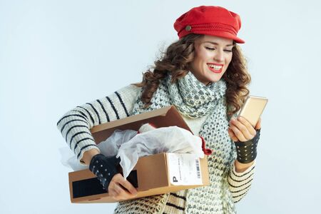 happy elegant woman with long brunette hair in sweater, scarf and red hat holding opened parcel and using smartphone app against winter light blue background.