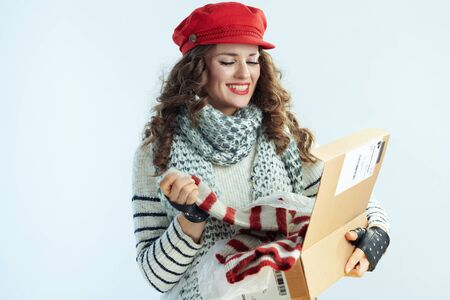 happy young woman with long brunette hair in sweater, scarf and red hat holding opened parcel and checking delivered sweater on winter light blue background. Фото со стока