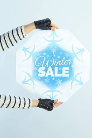 Closeup on young female with long brunette hair in sweater, scarf and red hat showing winter sale banner against winter light blue background.