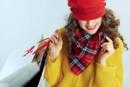 trendy middle age woman with long brunette hair in sweater, scarf and red hat with shopping bags on winter light blue background.