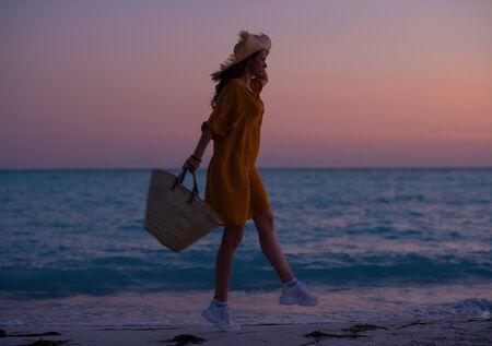 Silhouette de femme moderne aux longs cheveux bruns avec sac de plage sautant sur la côte de l'océan au coucher du soleil.