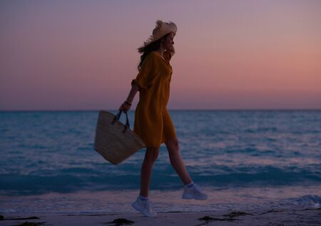 Silhouette of modern woman with long brunette hair with beach bag jumping while on the ocean coast at sunset.