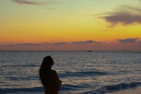 Silhouette of modern woman with long brunette hair on the seacoast at sunset looking into the distance.