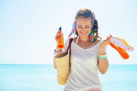 happy trendy woman in white t-shirt with beach straw bag, orange flip flops and bottle of sunscreen on the seashore.