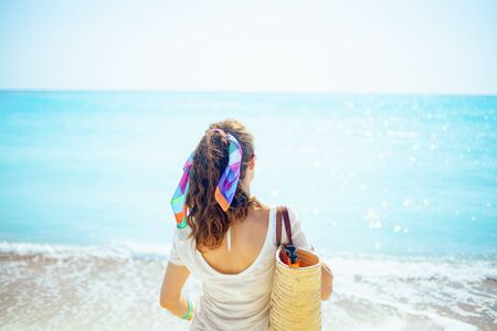 Seen from behind trendy woman in white t-shirt with beach straw bag on the ocean coast. Stock Photo