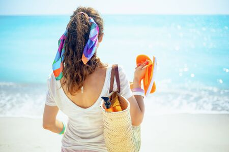 Seen from behind trendy 40 year old woman in white t-shirt with beach straw bag, orange flip flops and bottle of spf on the ocean shore.