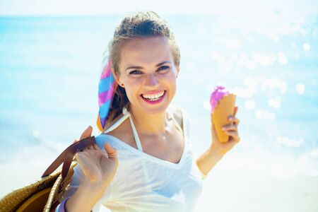 Portrait of smiling trendy woman in white t-shirt with beach straw bag holding ice cream on the seashore.