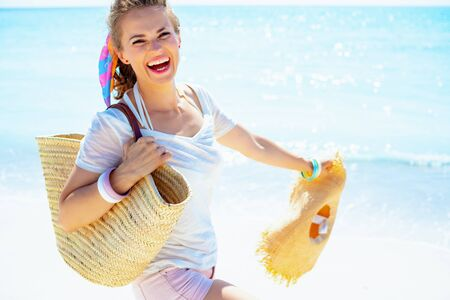 happy young woman in white t-shirt with beach straw bag and big hat on the seacoast.