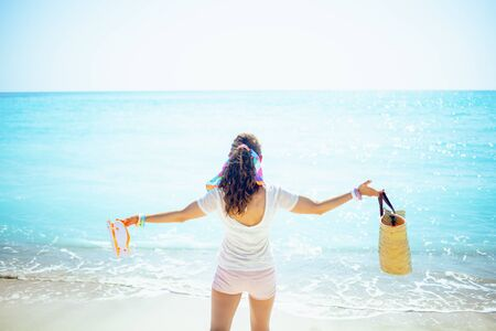 Seen from behind trendy woman in white t-shirt with beach straw bag and orange flip flops with raised arms rejoicing on the seacoast.