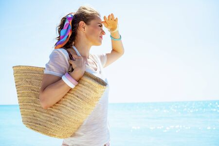 trendy woman in white t-shirt with beach straw bag looking into the distance on the ocean shore. Stockfoto