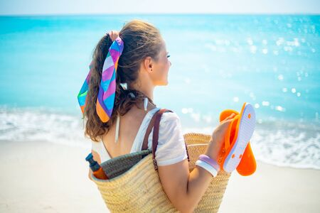 Seen from behind modern woman in white t-shirt with beach straw bag, orange flip flops and bottle of spf looking into the distance on the beach.