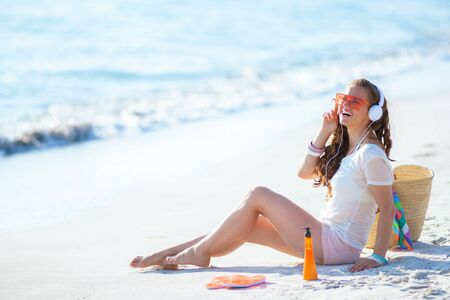 smiling healthy 40 year old woman in white t-shirt and pink shorts listening to the music with headphones while sitting on the beach.
