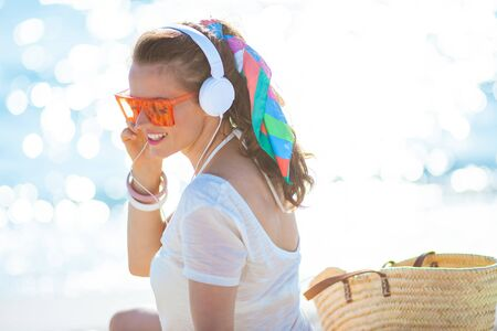 smiling trendy woman in white t-shirt and pink shorts listening to the music with headphones on the ocean coast.