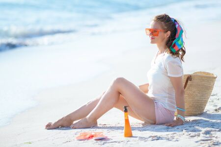 relaxed young woman in white t-shirt and pink shorts sitting on the seashore.