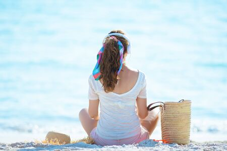 Seen from behind young woman in white t-shirt and pink shorts listening to music with headphones and sitting on the ocean shore.