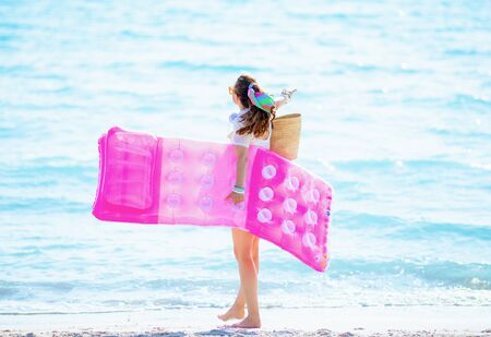 Seen from behind 40 year old woman in white t-shirt and pink shorts with beach straw bag on the beach rejoicing while holding inflatable mattress. Stock Photo